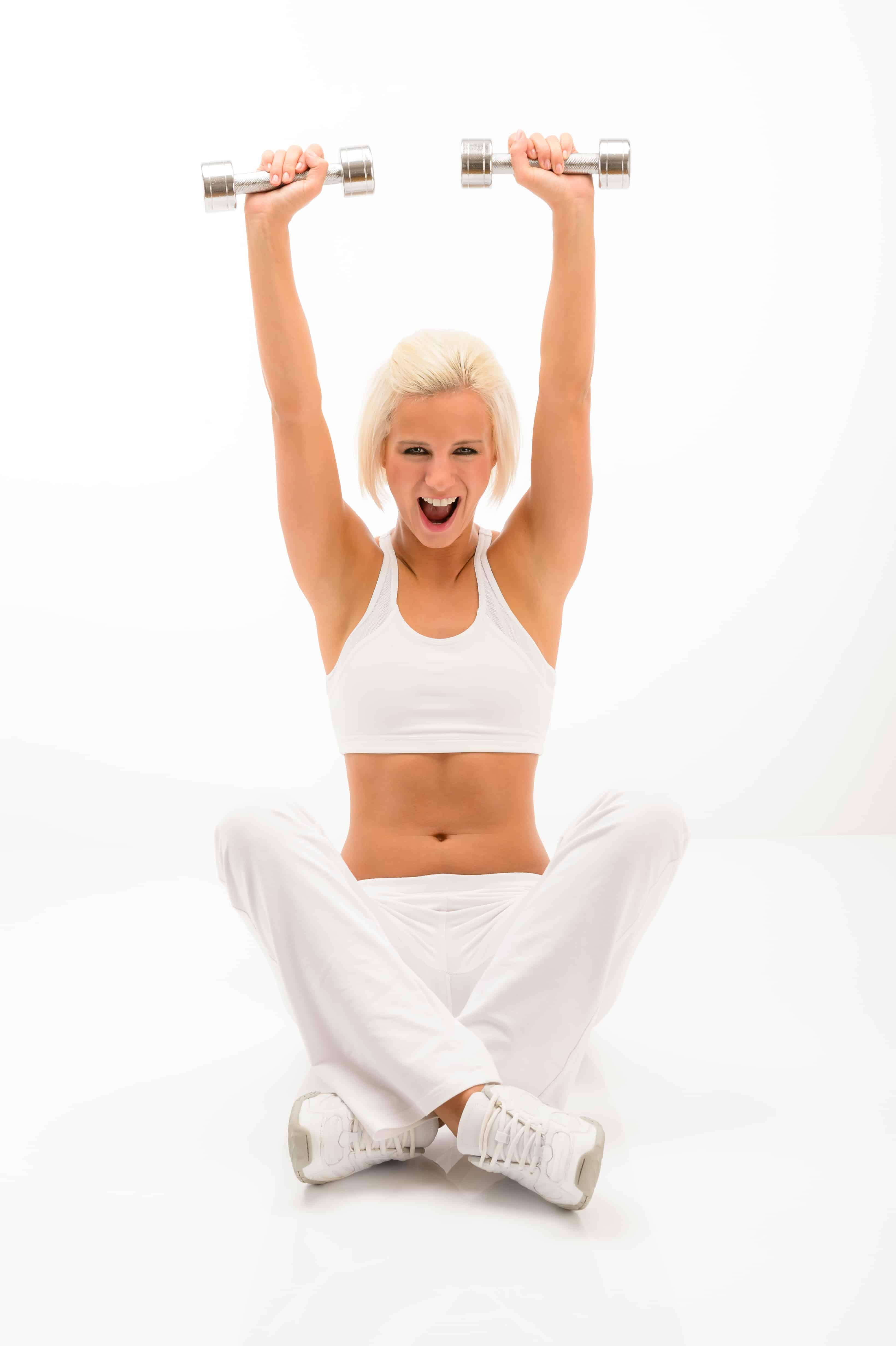 Fitness woman exercise in studio lifting dumbbells sitting white floor